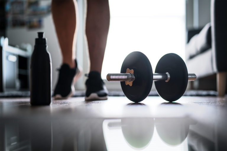 Fitness, home workout and weight training concept. Man starting to exercise with dumbbell. Water or protein shake bottle on floor.